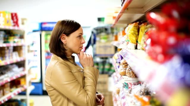 상점에서 쇼핑 하는 여자 - 검사 보기 스톡 비디오 및 b-롤 화면