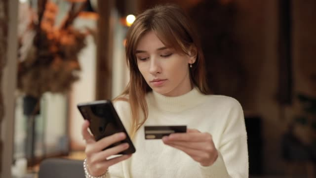 Woman shopping online paying with credit card in cafe video