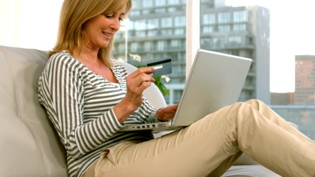 kvinna shopping på nätet med sin laptop - spendera pengar bildbanksvideor och videomaterial från bakom kulisserna