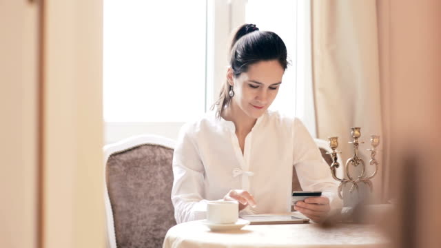 Woman shopping online with tablet. through glass video