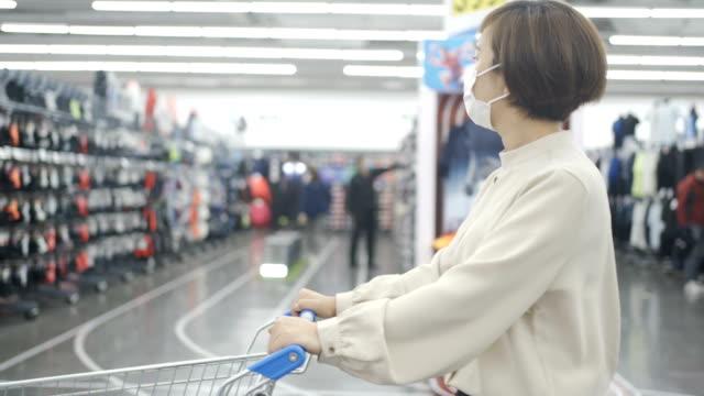 donna shopping con maschera - consumismo video stock e b–roll