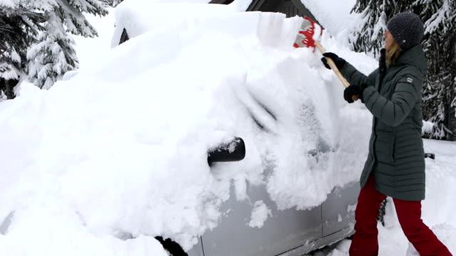 kvinna skotta snö på framsidan av bilen. - skyffel bildbanksvideor och videomaterial från bakom kulisserna