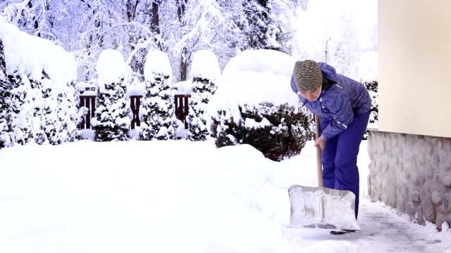 kvinna som skotta snö nära hennes out-of-town hus efter ett intensivt snöfall - skyffel bildbanksvideor och videomaterial från bakom kulisserna