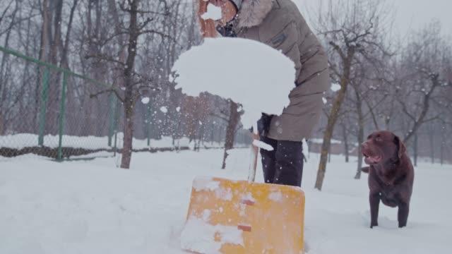 SLO MO Woman shovelling the snow