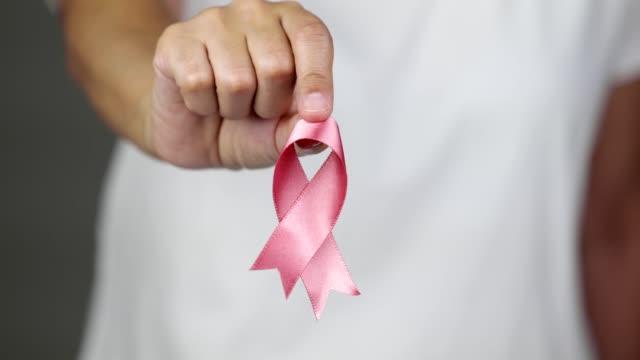 kameraya doğru pembe meme kanseri farkındalık kurdelesi gösteren kadın - ribbon stok videoları ve detay görüntü çekimi