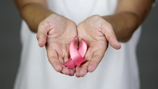 Woman showing a pink breast cancer awareness ribbon towards the camera Woman is holding pink breast cancer awareness ribbon. She reaches the ribbon towards the camera. mammogram stock videos & royalty-free footage