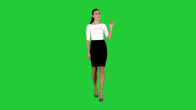 kvinna som visar och presenterar kopierings utrymme i affärs klänning på en grön skärm, chroma key - kostym sida bildbanksvideor och videomaterial från bakom kulisserna