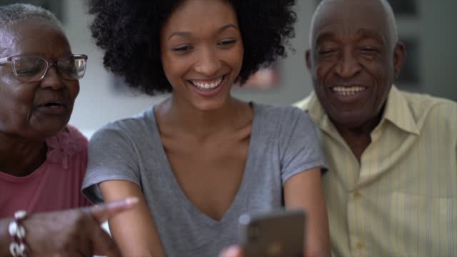 Woman showing cellphone to senior couple, people smiling and having fun