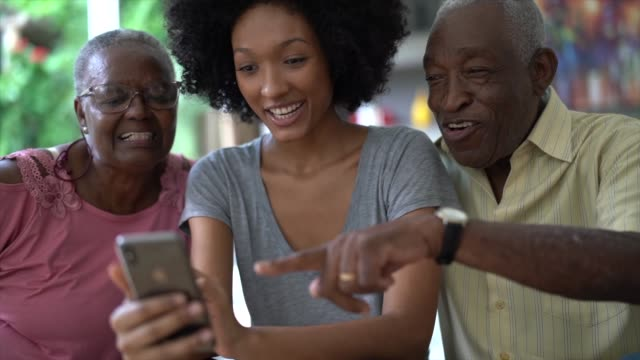 Woman showing cellphone to senior couple, people smiling and having fun Woman showing cellphone to senior couple, people smiling and having fun granddaughter stock videos & royalty-free footage