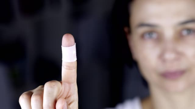 Woman showing finger with bandage, patch