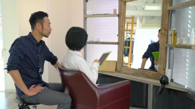 デジタル タブレットの髪のドレッサーのアイデアを示す女性 - 美容院点の映像素材/bロール