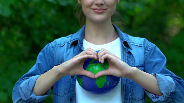 kvinna som visar hjärtat gest på jorden globe, planet care, miljömedvetenhet - recycling heart bildbanksvideor och videomaterial från bakom kulisserna