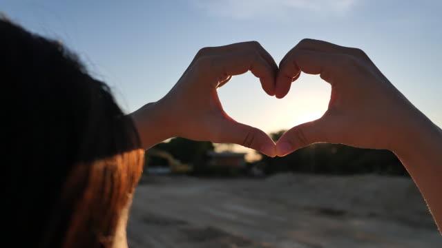 vídeos y material grabado en eventos de stock de mujer mostrando manos del corazón con el amanecer, planificación de la inversión de la casa. - planificación financiera
