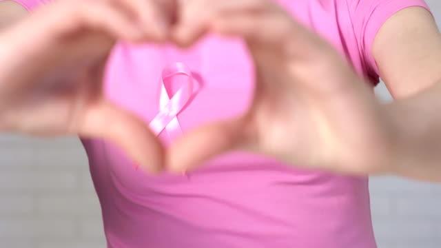 kadın kalp işareti çerçeveleme meme kanseri bilinçlendirme şerit - meme kanseri bilinçlendirme kavramı gösterilen - meme hayvan vücudu bölümleri stok videoları ve detay görüntü çekimi