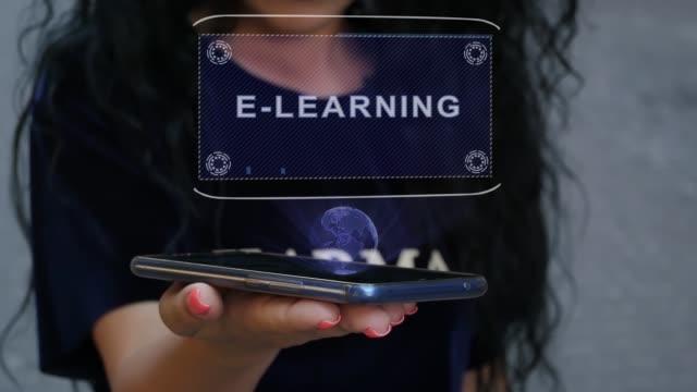 vidéos et rushes de femme affichant l'hologramme de hud e-learning - étudiant(e)