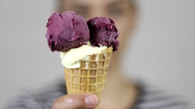 Woman showing ice cream in cone