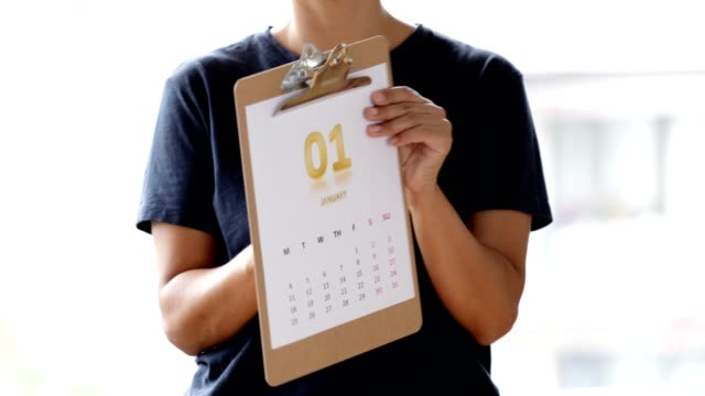 Woman showing monthly calendar of January