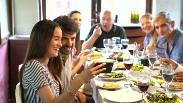 vídeos y material grabado en eventos de stock de mujer mostrando fotos en el teléfono mientras que el almuerzo familiar en el restaurante - memorial day weekend