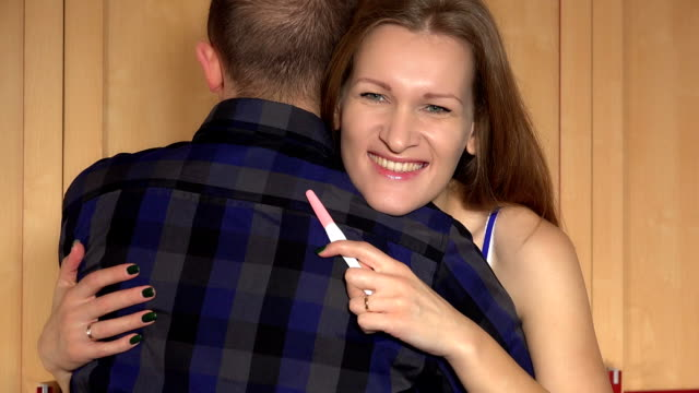 Woman showing positive emotions looking at camera. Pregnancy test - vídeo