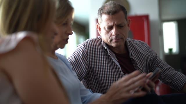 カップルにスマートフォンで何かを示す女性 - 親族会点の映像素材/bロール