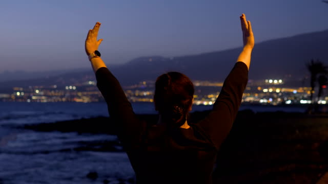 Woman showing symbol of freedom at the sunset in 4k slow motion 60fps