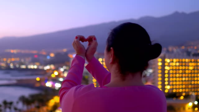 Woman showing symbol of love at the sunset in 4k slow motion 60fps