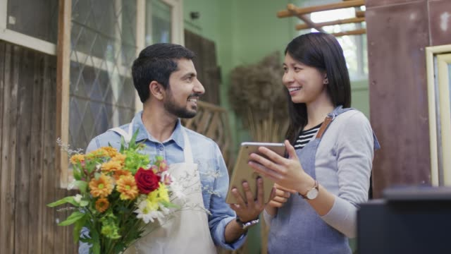 Woman showing tablet to ethnic male owner of a flower shop video