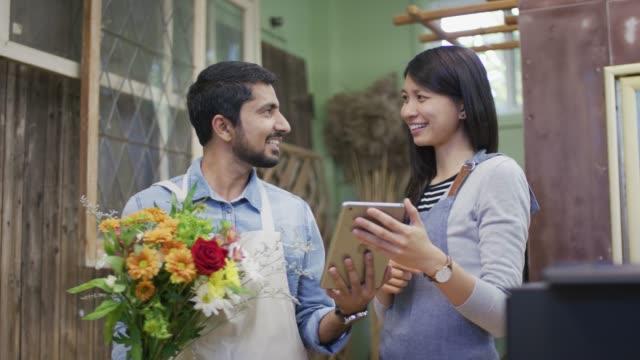 vidéos et rushes de tablette montrant femme ethnique mâle propriétaire d'un magasin de fleurs - relation client