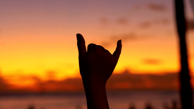 Woman Showing The Shaka hawaii love symbol at sunset in 4K Slow motion 60fps