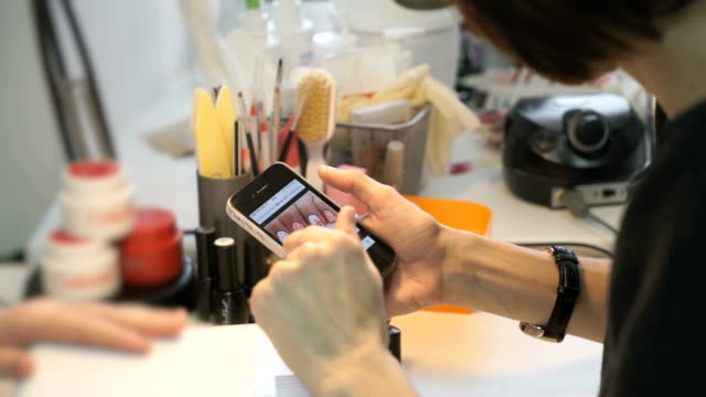 Woman shows on a phone a sample of the manicure Woman wizard shows on the smart phone a sample of the manicure girl at stylish women's the beauty salon. Hands closeup painting art product stock videos & royalty-free footage