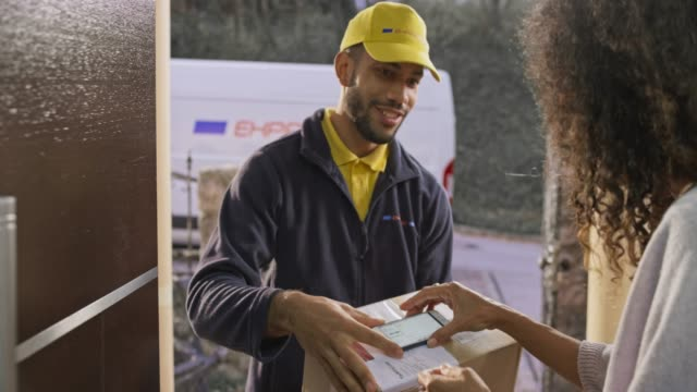 Woman signing for the package being delivered to her front door by a smiling male courier