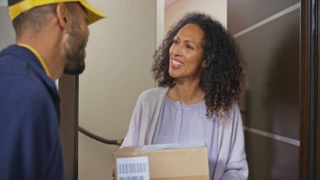 woman signing for the package delivery at the front door of her house - ricevere video stock e b–roll