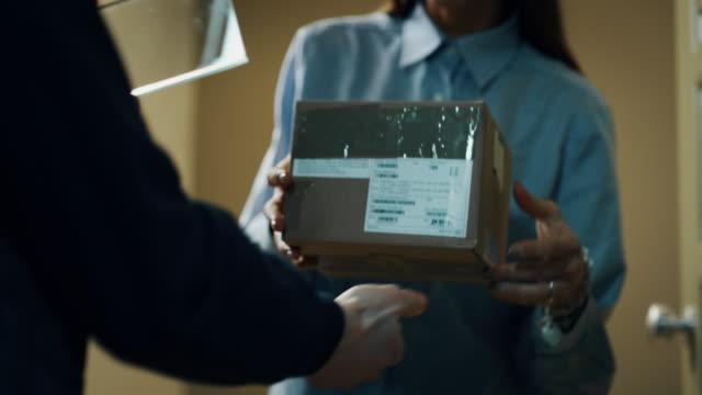婦女簽署未來增強現實傳送設備從郵遞員在她的家交付的包裹。 - postal worker 個影片檔及 b 捲影像
