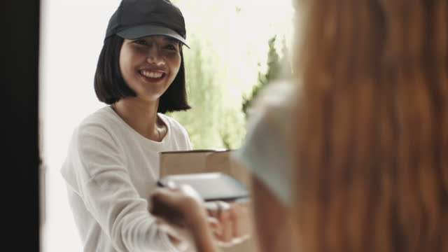 Woman signing on Smart phone for the package being delivered to his front door by a male courier
