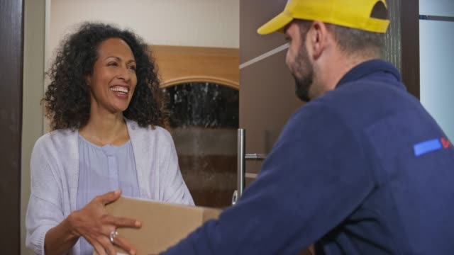 Woman signing the digital POD before the male courier hands her the package at the front door
