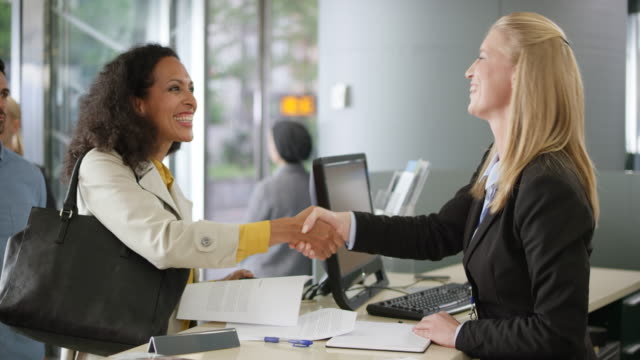 Woman signing the documents and the female car rental agent handing her the key to the car video