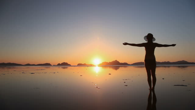 Woman silhouette arms raised on beach at sunset video
