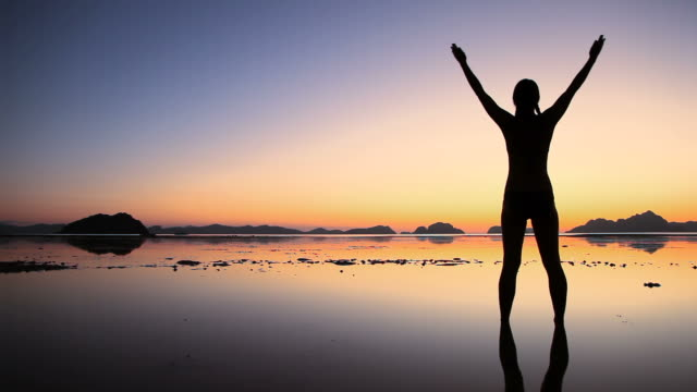 Woman silhouette arms raised on beach at twilight video