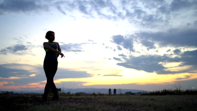 Woman silhouette dancing at sunset