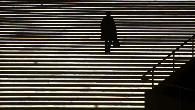 Woman silhouette on a stairway lights video