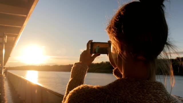 女性シルエットはクルーズ船の甲板上のスマート フォンで夕日の写真を撮影 - デッキ点の映像素材/bロール