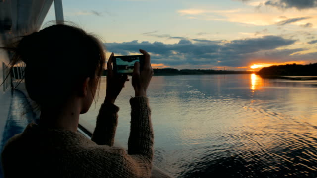 woman silhouette taking photo of sunset with smartphone on deck of cruise ship - cruise video stock e b–roll