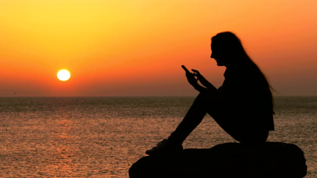 Woman silhouette using smart phone on the beach