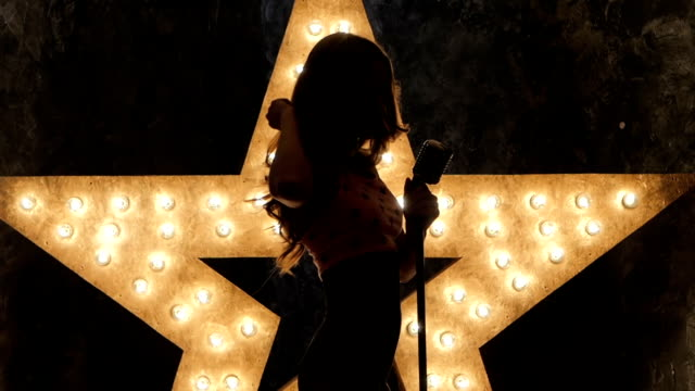 woman singer with microphone, shining star in the background. close up. silhouette, slow motion - steampunk fashion stock videos and b-roll footage
