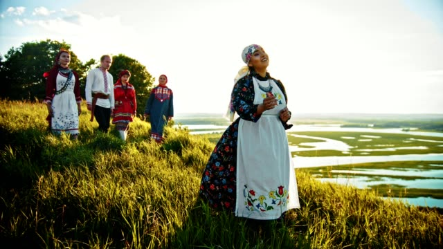a woman singing a song in russian traditional clothes standing on the field - other people come closer to her. - славянская культура стоковые видео и кадры b-roll