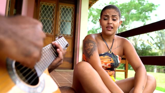 Woman singing and man playing acoustic guitar