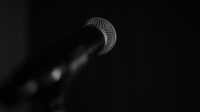 A woman singing into a microphone, tone rehearsal before a performance