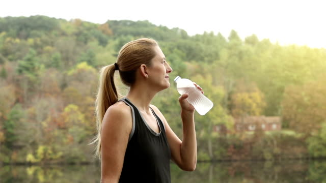 Woman Sipping Water Outdoors In Fall video