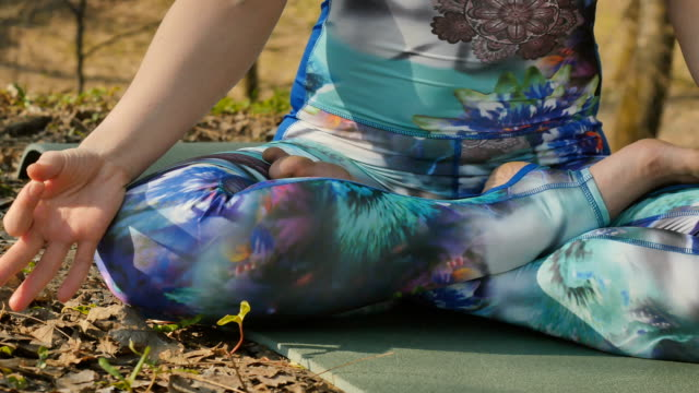 woman sits in lotus pose and meditating - gambe incrociate video stock e b–roll