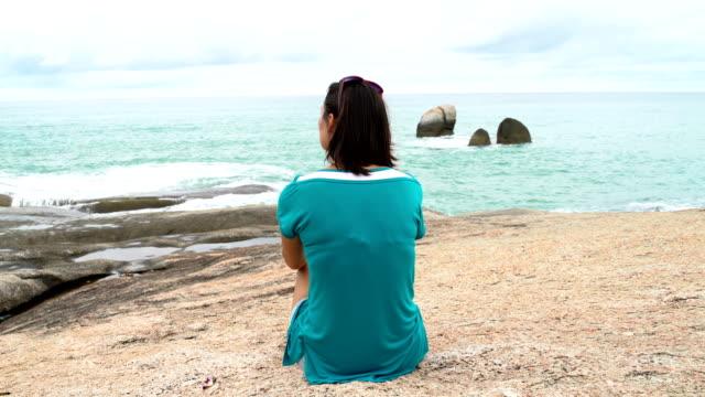 eine frau sitzt auf einem stein bank und blick auf das meer - haarfarbe stock-videos und b-roll-filmmaterial